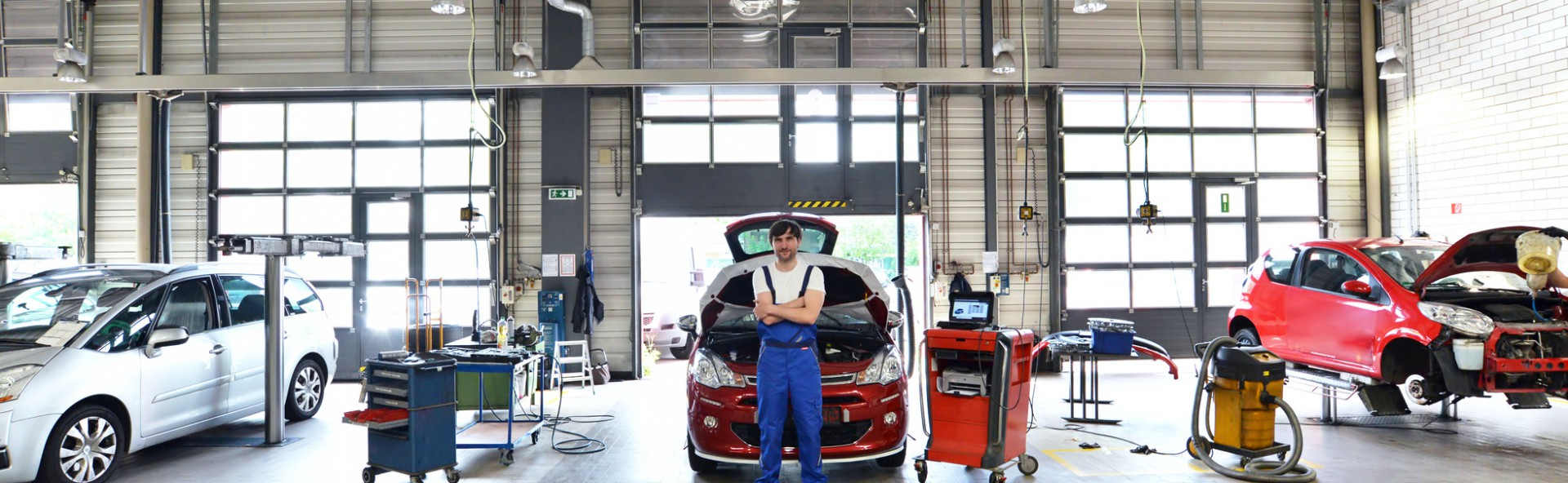 car mechanic in a garage with vehicles // moderne Autowerkstatt